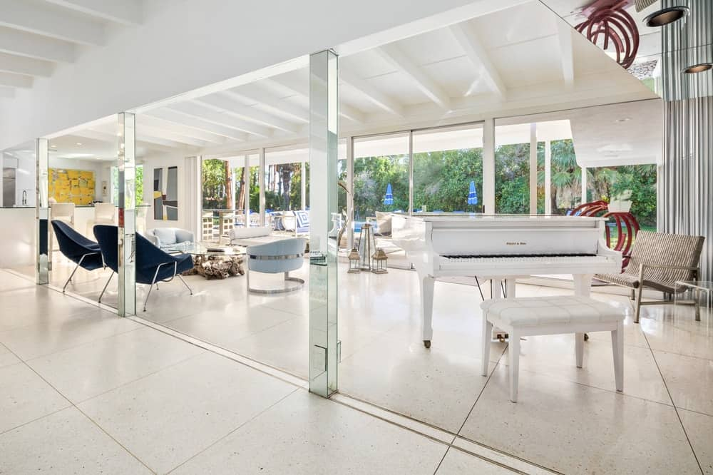 The famous white piano is just beside the bright living room with a few thin columns helping to support the large white ceiling with exposed white beams. Images courtesy of Toptenrealestatedeals.com.