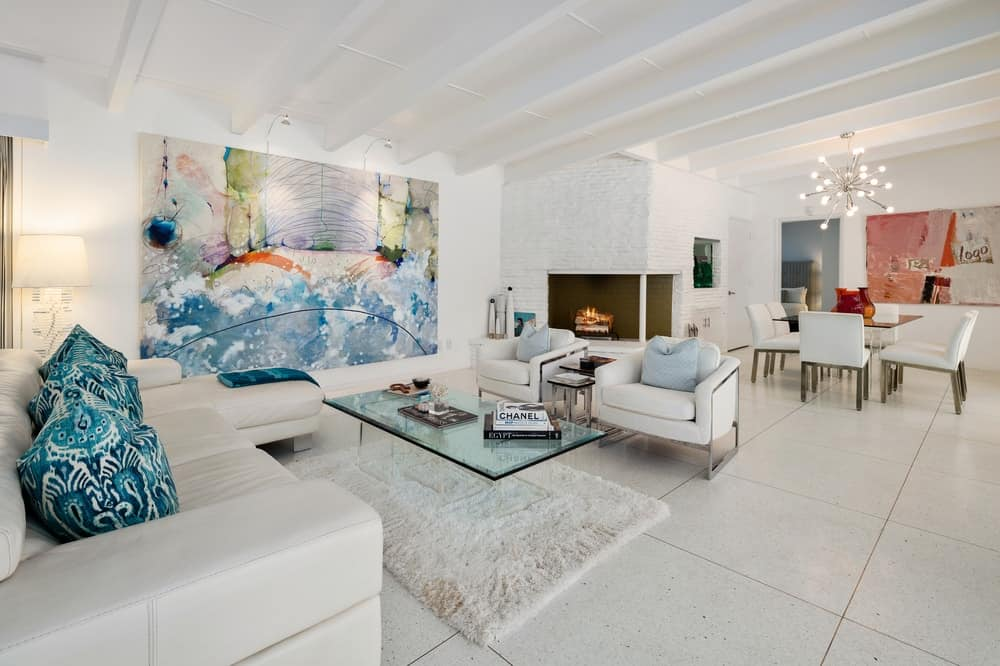 This living room's beige sofa set is complemented by the large wall-mounted colorful artwork that stands out against the white wall. Images courtesy of Toptenrealestatedeals.com.