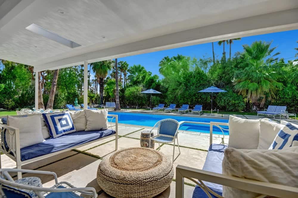 Just a few steps from the pool side area is this relaxing covered patio with a tall white ceiling paired with concrete slab flooring. Images courtesy of Toptenrealestatedeals.com.