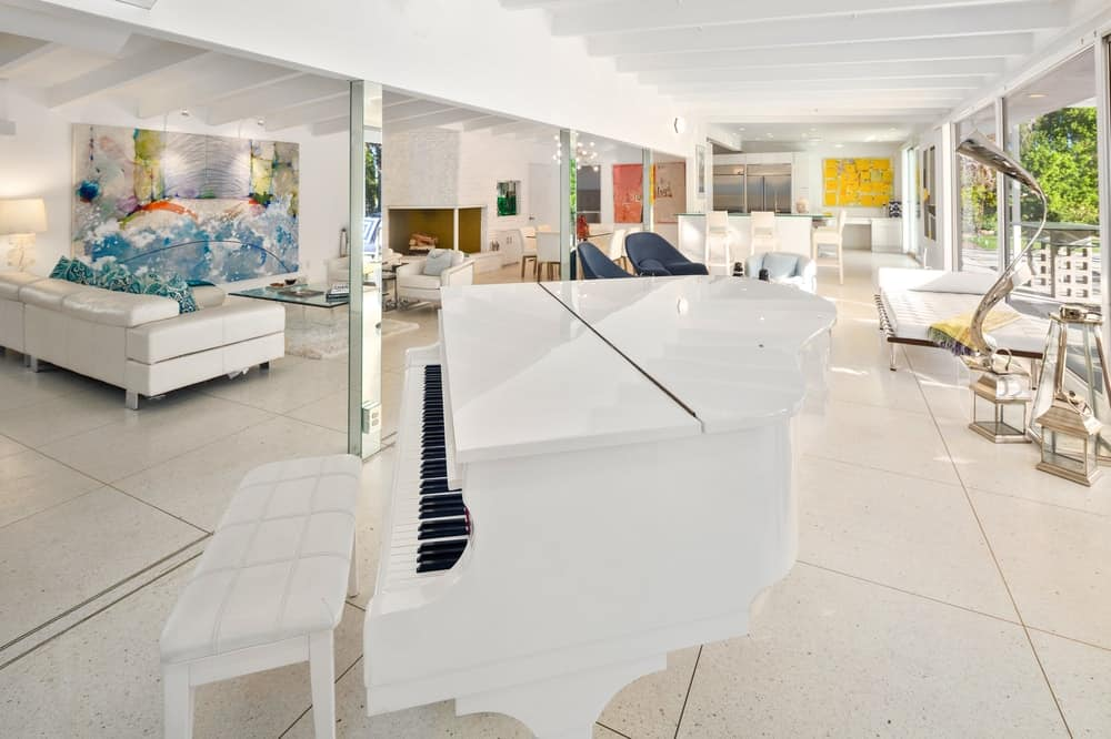 This beautiful piano is placed inside a large great room that has several comfortable areas brightened by the large glass walls bringing in natural lighting. Images courtesy of Toptenrealestatedeals.com.