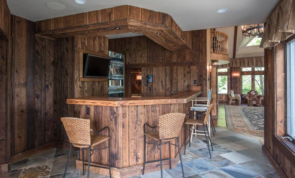 A look at the home's bar area with wooden walls and a wooden bar counter. Images courtesy of Toptenrealestatedeals.com.