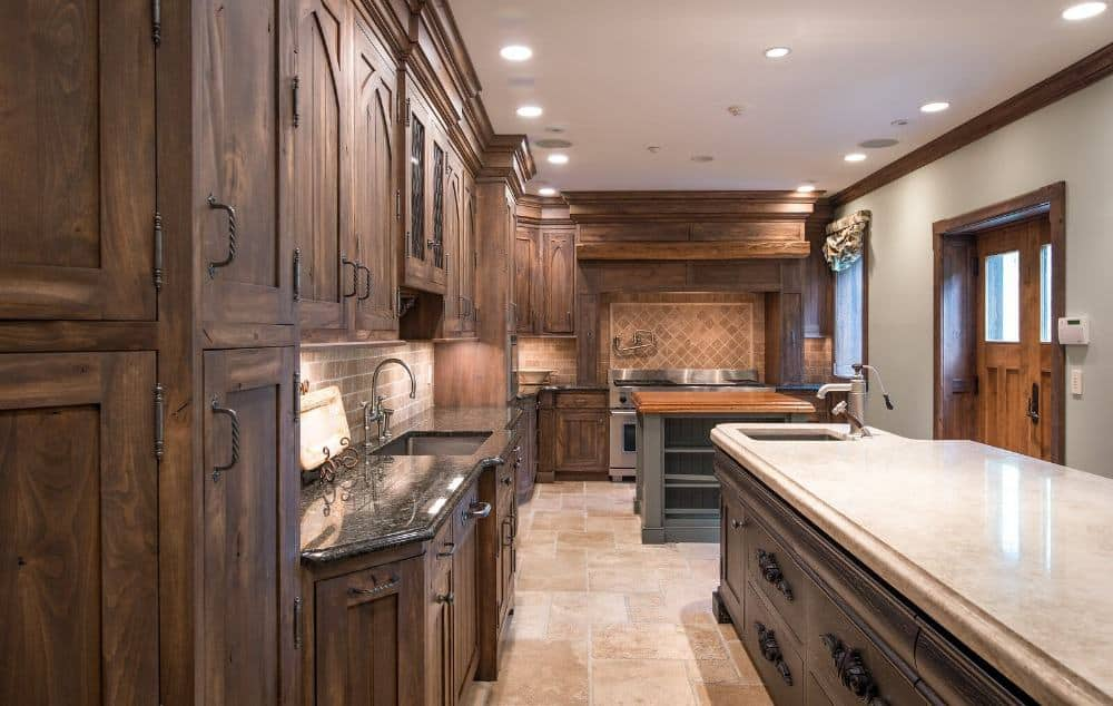 This kitchen features brown cabinetry and kitchen drawers, along with a black marble countertop. There are two center islands as well. Images courtesy of Toptenrealestatedeals.com.