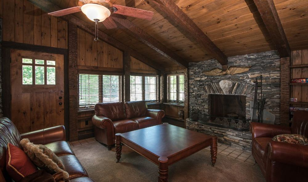 A living space with rustic walls and ceiling. It offers a set of leather seats and a stone fireplace. Images courtesy of Toptenrealestatedeals.com.