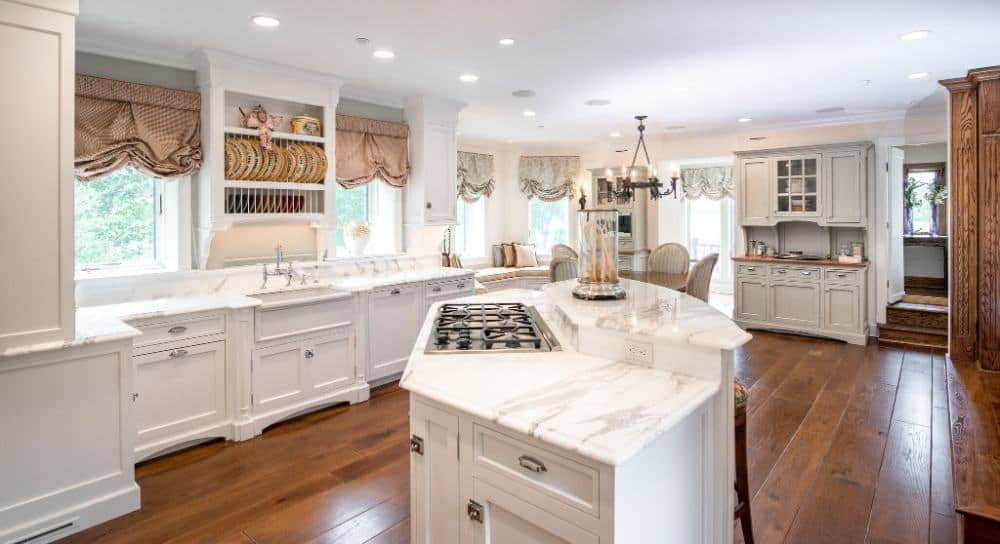 This kitchen features white kitchen counter and cabinetry, along with a white custom center island with a gorgeous countertop. Images courtesy of Toptenrealestatedeals.com.
