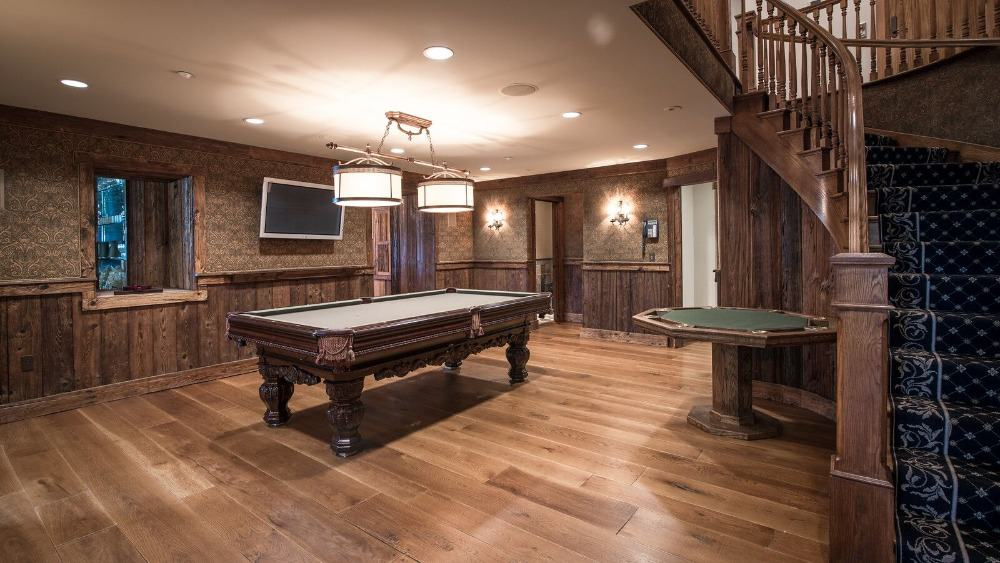 A game room with gorgeous brown walls and hardwood flooring. The room also offers a billiards table that looks classy. Images courtesy of Toptenrealestatedeals.com.