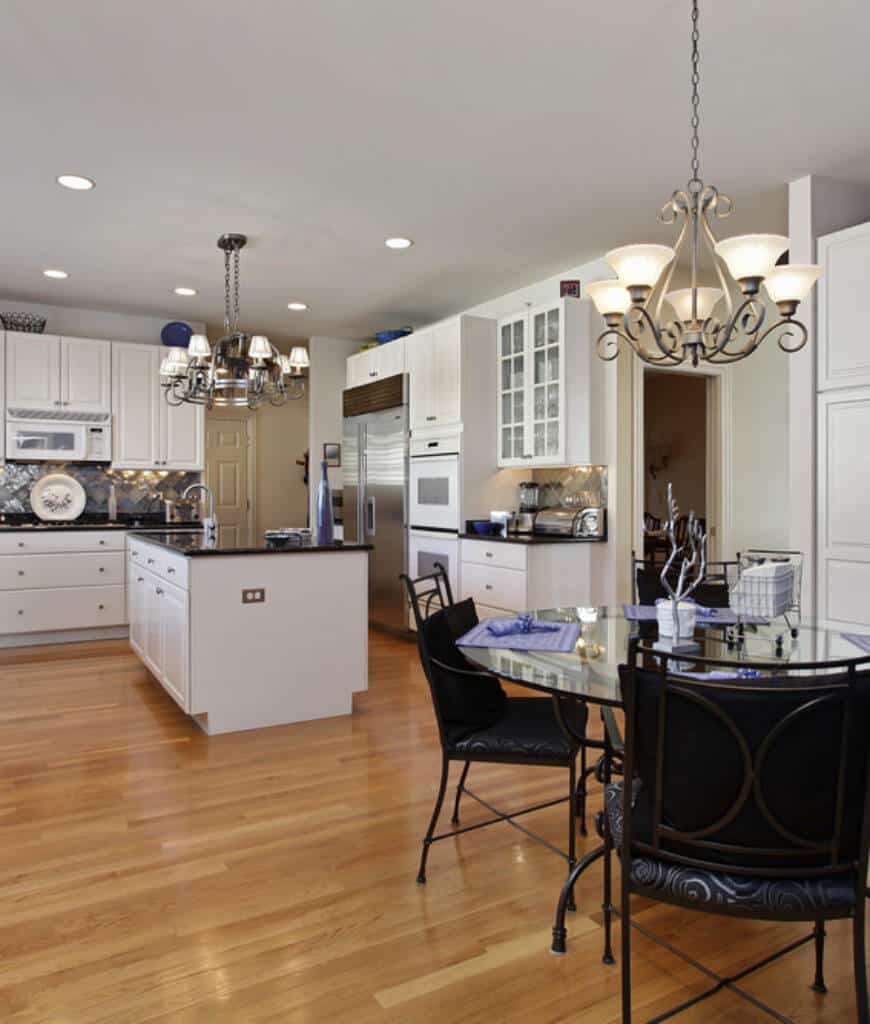 Spacious eat-in kitchen loaded up with white cabinetry that is flawlessly stood out from dark metal feasting set. It includes a glass front bureau and a couple of great crystal fixtures.