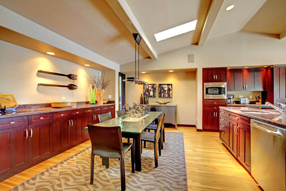 A dine-in kitchen highlighting ruddy wooden cabinetry and kitchen counters, alongside a glass top dining table set on a smart floor covering.