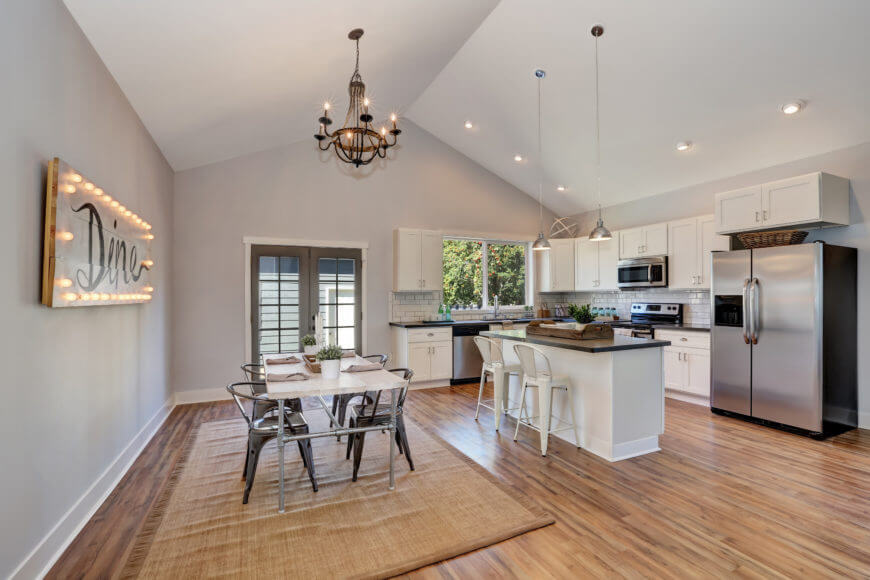 A dine-in kitchen highlighting a little breakfast bar and a dining table set lit by a stunning chandelier set on a white roof.