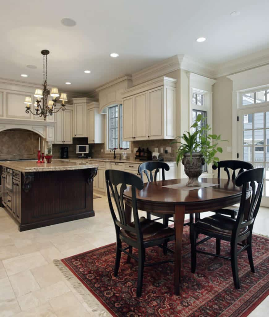 Dine-in kitchen with white cabinetry and a dim wood breakfast island over the wooden eating set on a red adorned mat.
