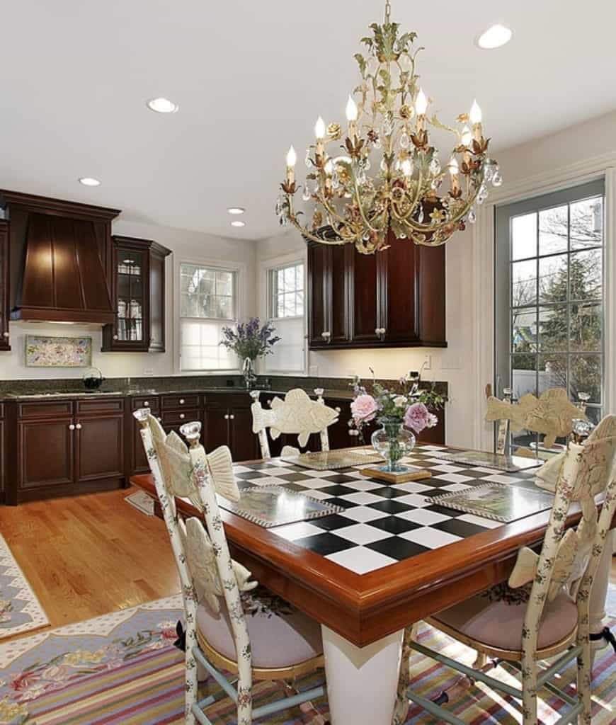 Astonishing kitchen highlights alluring chandelier and floral seats encompassing a checkered dining table on a bright striped carpet over wood board flooring.