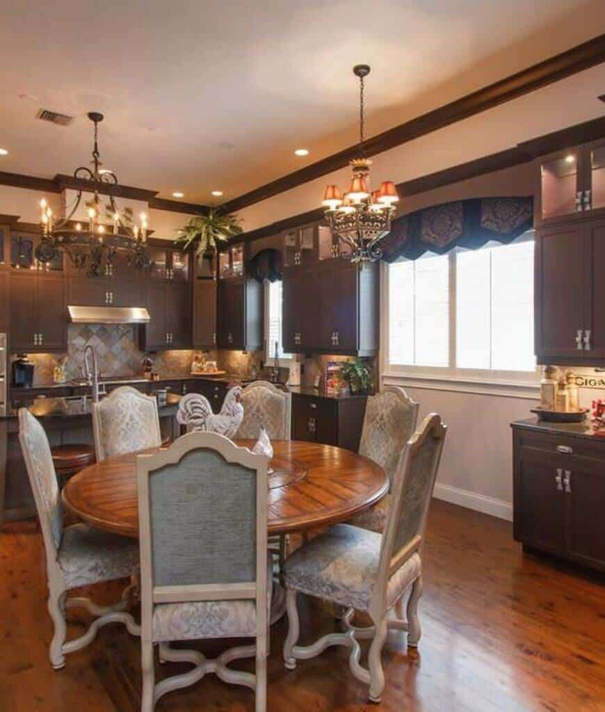 Warm eat-in kitchen outfitted with earthy colored cabinetry alongside a round dining table and dazzling high back seats over the rich hardwood flooring.