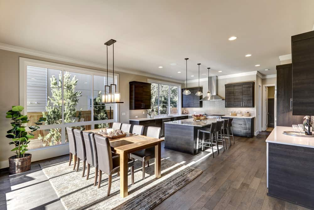 Huge dining kitchen including a breakfast bar and an 8-seater rectangular dining table set on the carpet covering the hardwood floors.