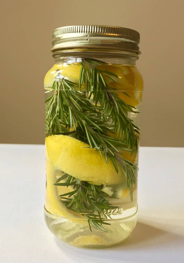 An all natural home made cleaner with lemon peel, fresh rosemary sprigs, and white vinegar in a clear glass mason jar.