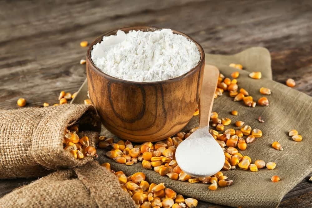 A wooden bowl of corn starch along with bags of corn kernels.