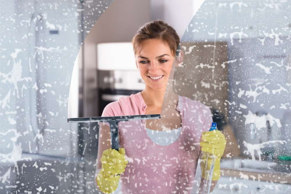 A woman cleaning the window with the use of a squeegee and a sprayer.