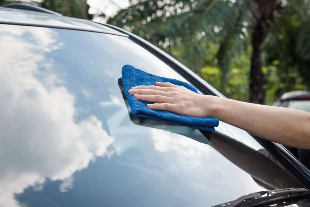 A man cleaning the windshield of a car using a microfiber cloth.