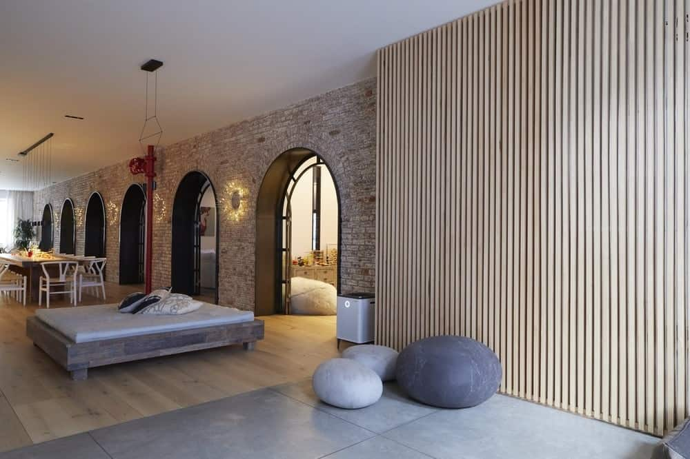 At the far end of the large hall is this area by the end of the arches accented with wood on the wall and adorned with decorative stones next to a day-bed with wooden frame. Images courtesy of Toptenrealestatedeals.com.
