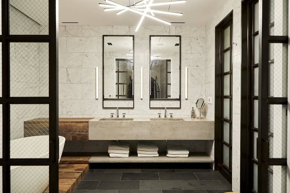 This is the bathroom that has a freestanding white porcelain bathtub raised on a wooden platform that matches with the edge of the two-sink vanity topped with wall-mounted mirrors. These are then topped with decorative lighting that brightens the charcoal gray flooring tiles. Images courtesy of Toptenrealestatedeals.com.