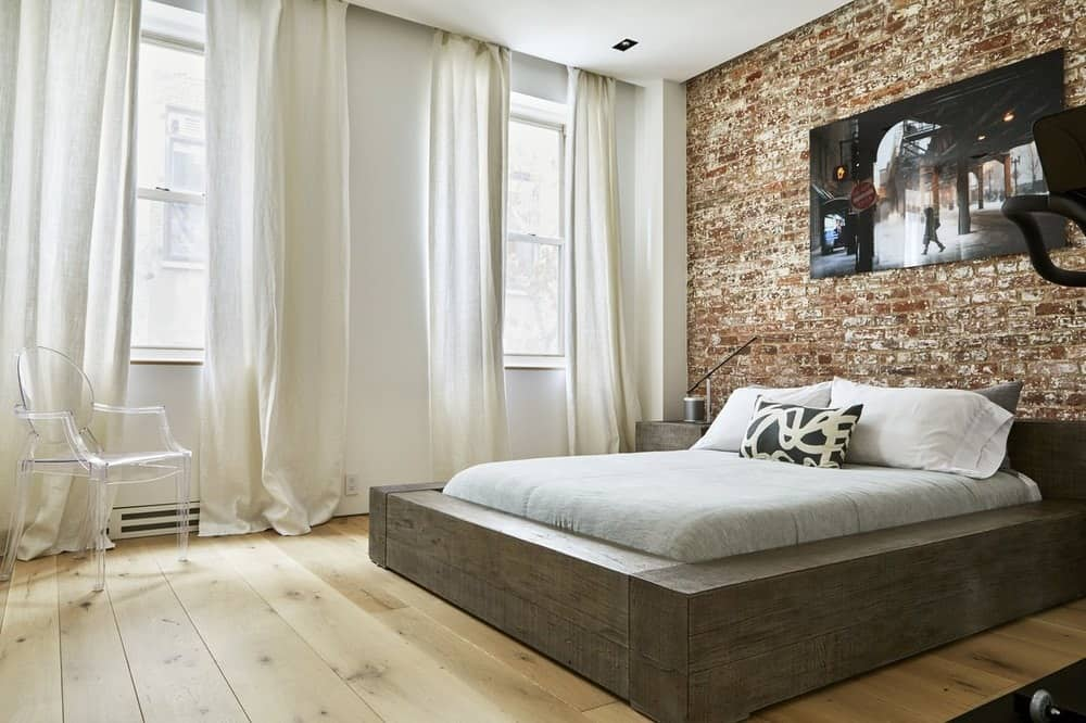 This bedroom has a gorgeous dark wooden bed frame that matches with the bedside drawers. This bed serves as a nice balance between the light hardwood flooring and the large red brick wall behind the head of the bed. These are then illuminated by the row of tall curtained windows on the side. Images courtesy of Toptenrealestatedeals.com.