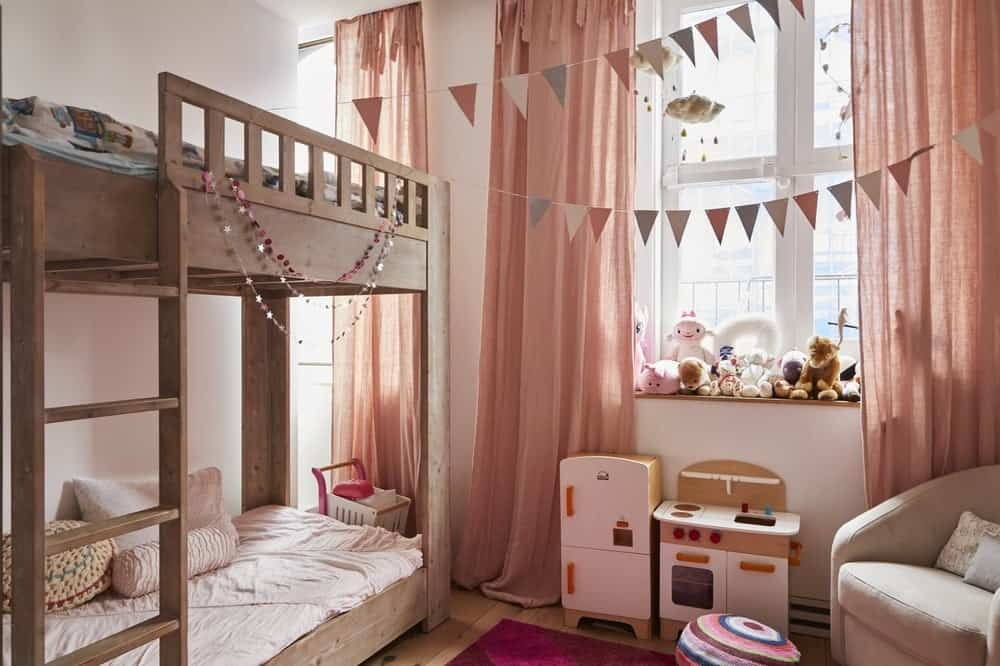 This beautiful girl's bedroom has cute salmon-colored curtains that pair well with the beige walls. These serve as a pleasing background for the for the wooden bunk bed that matches the shelf for the toys under the window by the cushioned arm chair. Images courtesy of Toptenrealestatedeals.com.