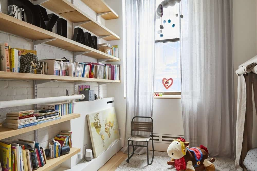 This lovely kid's bedroom also functions as a play room and nursery perfect for toddlers. The beige brick wall is adorned with floating wooden shelves filled with books and displays. Images courtesy of Toptenrealestatedeals.com.
