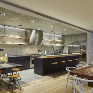 This angle shows the beauty of the contemporary design of the double-loft. It has a large kitchen with a breakfast bar and an informal dining area on the side with a booth-style built-in bench. Next to this is the long dining table for the formal dining area and at the far end, you can see the living room area. Images courtesy of Toptenrealestatedeals.com.