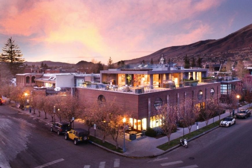 This is the aerial look at the beautiful penthouse in downtown Aspen. There are an abundance of glass walls and open walls that spill warm yellow lights on the deck of the penthouse.