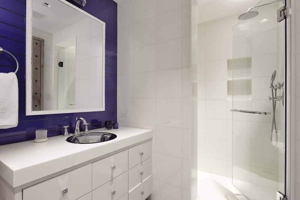 This simple bathroom has light tones to its walls, flooring and the vanity. These are then complemented by the lovely purple accent that surrounds the wall-mounted mirror above the white countertop of the vanity. Images courtesy of Toptenrealestatedeals.com.