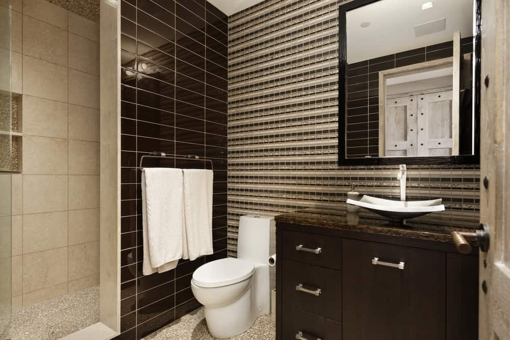 The dark cabinets and drawers of the vanity matches well with the wall tiles beside the white porcelain toilet mounted with towel racks. Images courtesy of Toptenrealestatedeals.com.