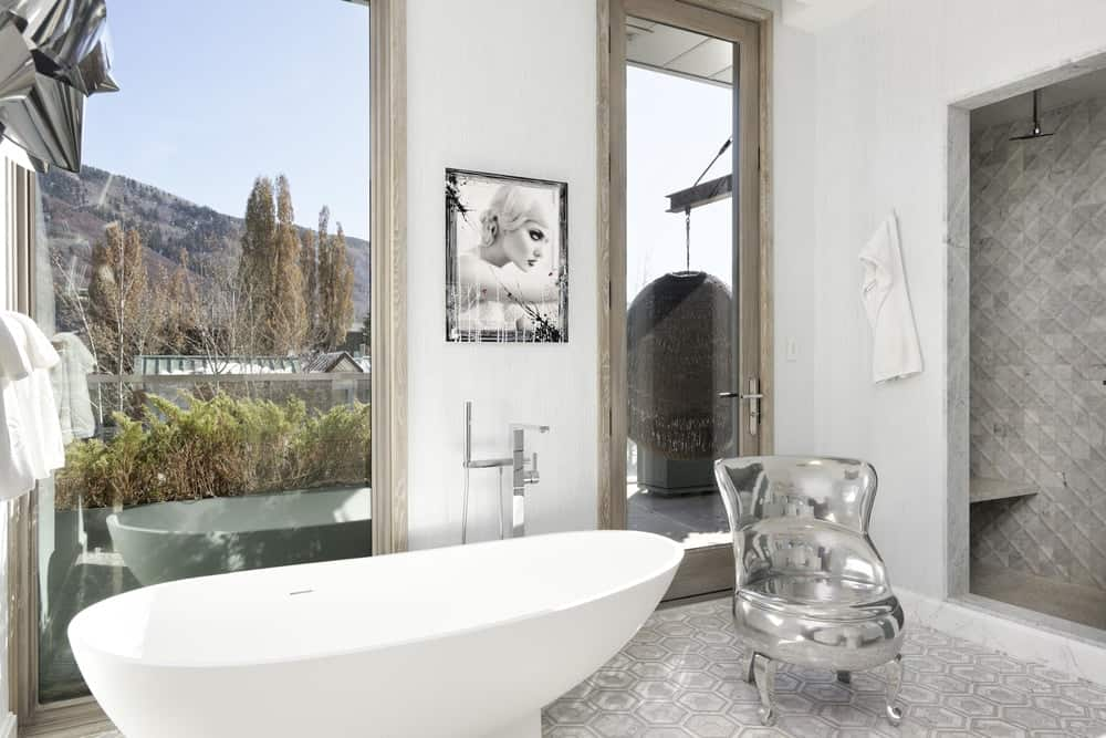 This bathroom has a freestanding white porcelain bathtub that is placed against a tall glass wall. There is also a modern silver chair beside the tub by the walk-in shower and the glass door to the balcony. Images courtesy of Toptenrealestatedeals.com.