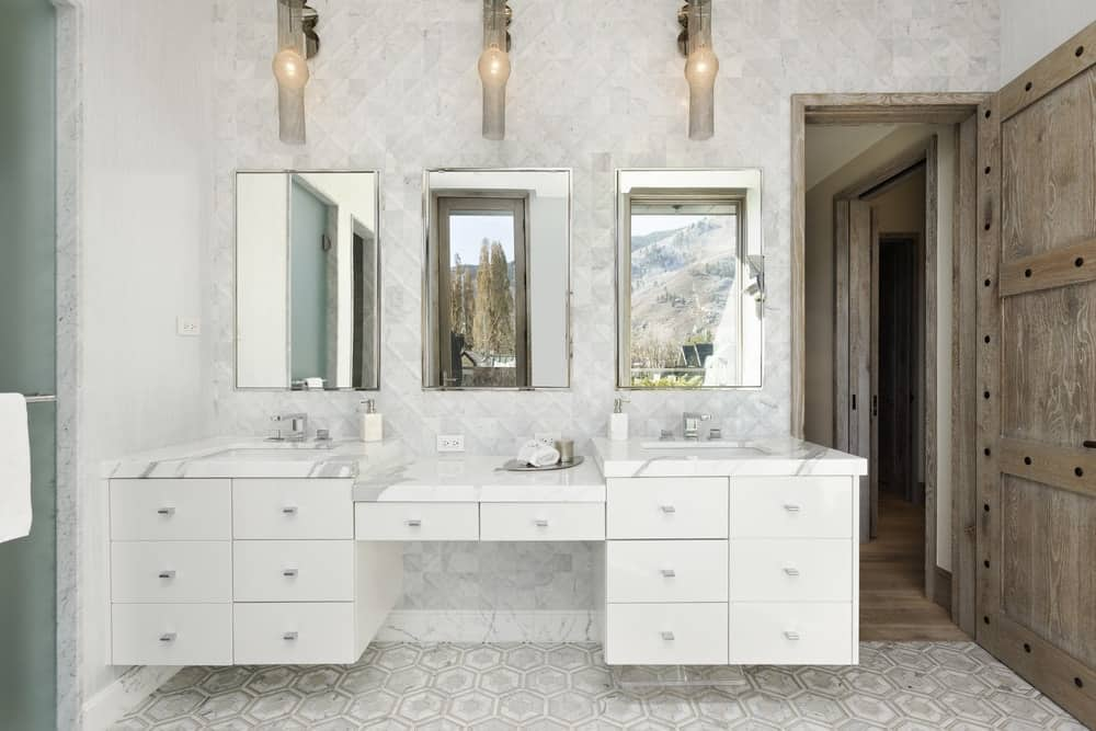 This bathroom has a large white wooden structure mounted on the wall for a floating design with sleek white drawers to match the white marble countertop with three wall-mounted mirrors above and wall-mounted lamps. Images courtesy of Toptenrealestatedeals.com.