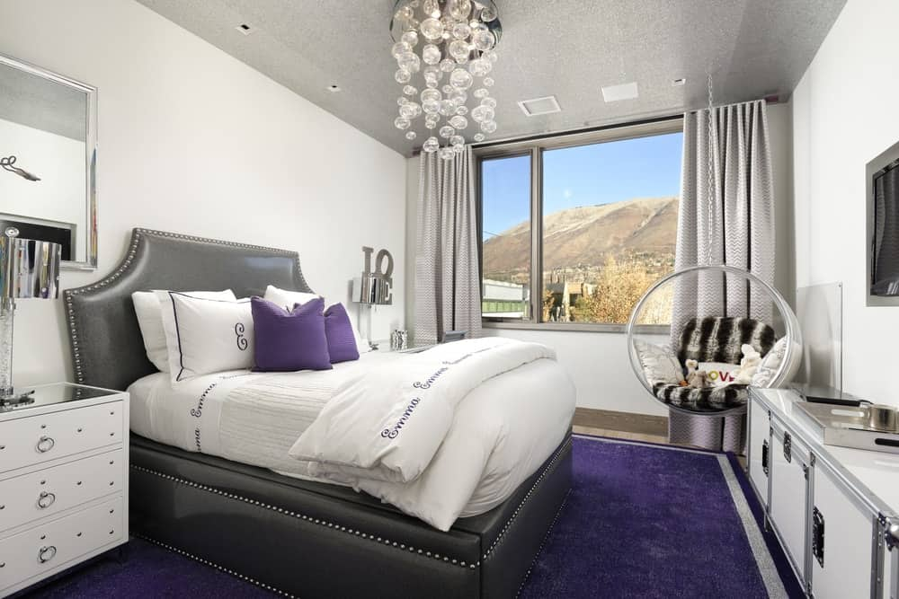 This bedroom has a dark gray cushioned bed frame that stands out against the deep purple carpeting of the floor paired with purple pillows and topped with a lovely and decorative lighting from the ceiling. Images courtesy of Toptenrealestatedeals.com.