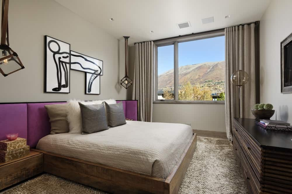 This bedroom has a large wooden platform bed paired with a large headboard that has purple cushions extending to the bedside drawers. This headboard is topped with a simple wall-mounted artwork. that stands out against the beige walls and ceiling. Images courtesy of Toptenrealestatedeals.com.