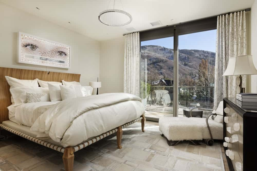 This bedroom has a large wooden bed topped with a colorful wall-mounted artwork and a round chandelier from the beige ceiling. On the side of the bed is a large sliding glass wall with access to a balcony. Images courtesy of Toptenrealestatedeals.com.