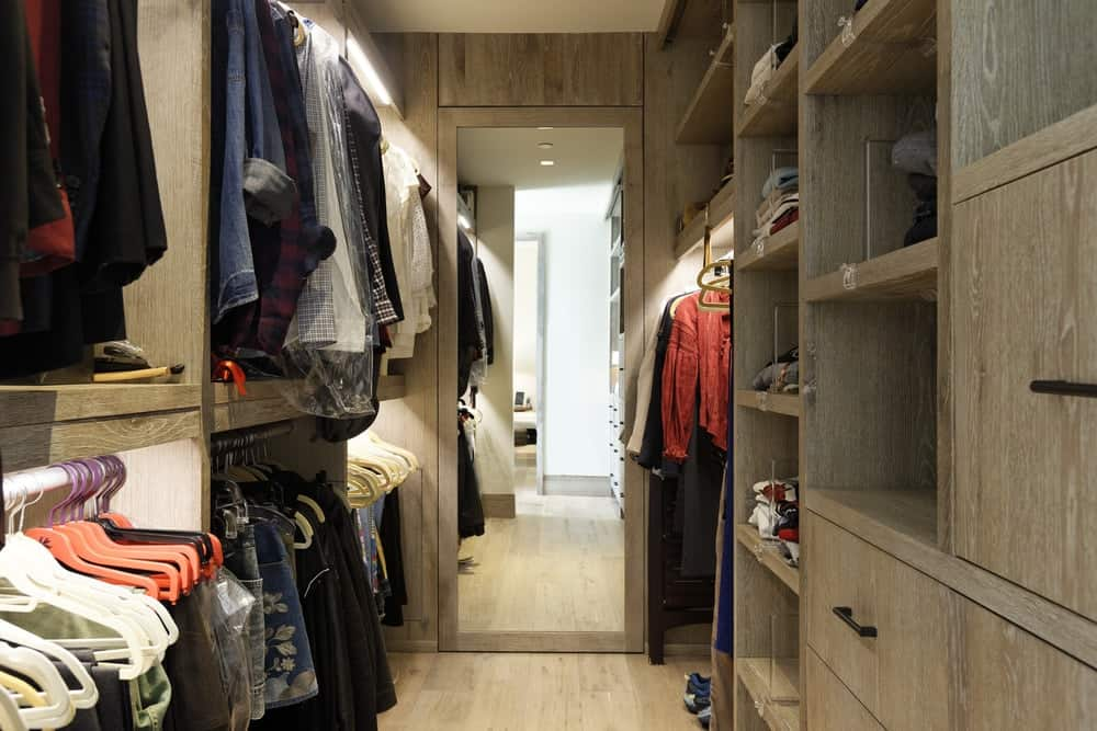 This is the lovely walk-in closet with rows of clothes racks as well as built in wooden drawers and shelves lining the walls and on the far wall is a large mirror. Images courtesy of Toptenrealestatedeals.com.