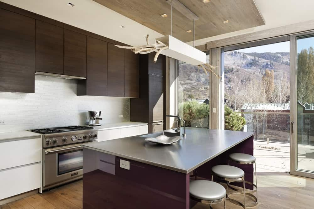 The kitchen has a sleek purple kitchen island topped with a stainless steel countertop and a unique decorative lighting above with wooden branches. hanging from the wooden ceiling. Images courtesy of Toptenrealestatedeals.com.