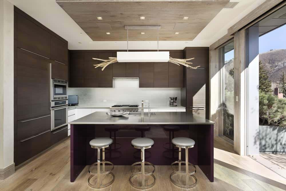 This unique and sleek kitchen island is paired with three modern stools as well as surrounded by dark brown cabinetry of the kitchen that houses the appliances brightened by the large glass walls on the side. Images courtesy of Toptenrealestatedeals.com.