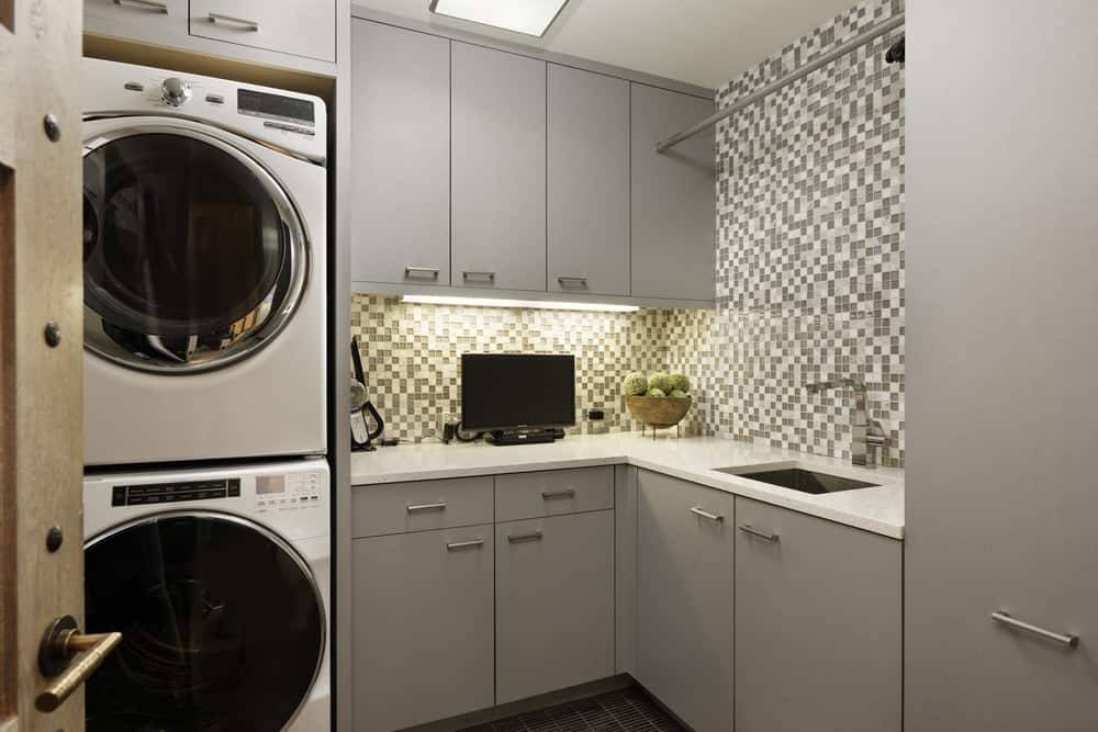 This is the laundry room with light gray cabinetry to match the gray patterned walls with a sink. The room is dominated by the two large modern machines placed on a stack at the edge of the cabinets. Images courtesy of Toptenrealestatedeals.com.