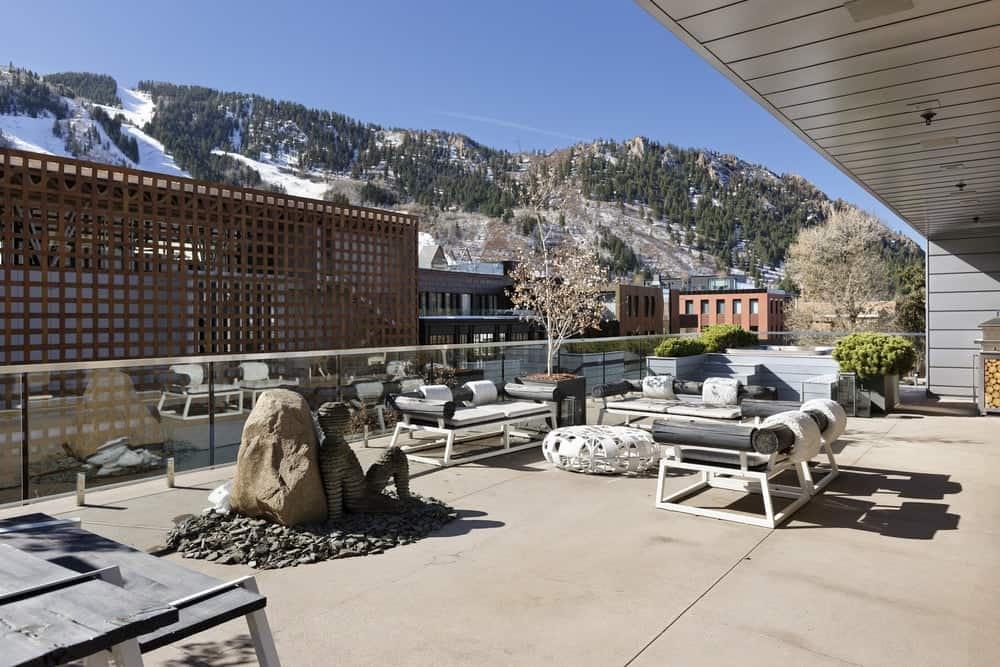 This is the deck and patio of the penthouse with comfortable modern outdoor furniture adorned with a large decorative stone in the middle paired with sculpture. Images courtesy of Toptenrealestatedeals.com.