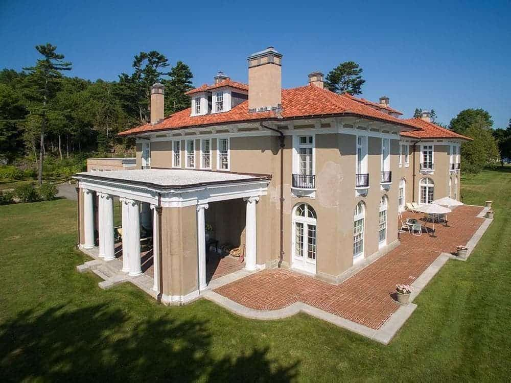 This view of the house gives us a closer look at its elegant beige exterior walls that are complemented by the surrounding terracotta walkways and green landscaping that has lawns of green grass and tall trees. Images courtesy of Toptenrealestatedeals.com.