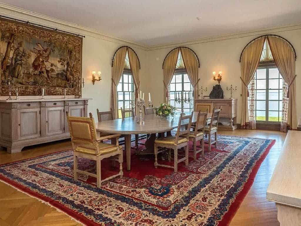 The large wooden dining table and wooden dining chairs of this formal dining area stands out against the colorful patterned area rug of the hardwood flooring. The dining area is also adorned with tall arched windows and a large artwork. Images courtesy of Toptenrealestatedeals.com.