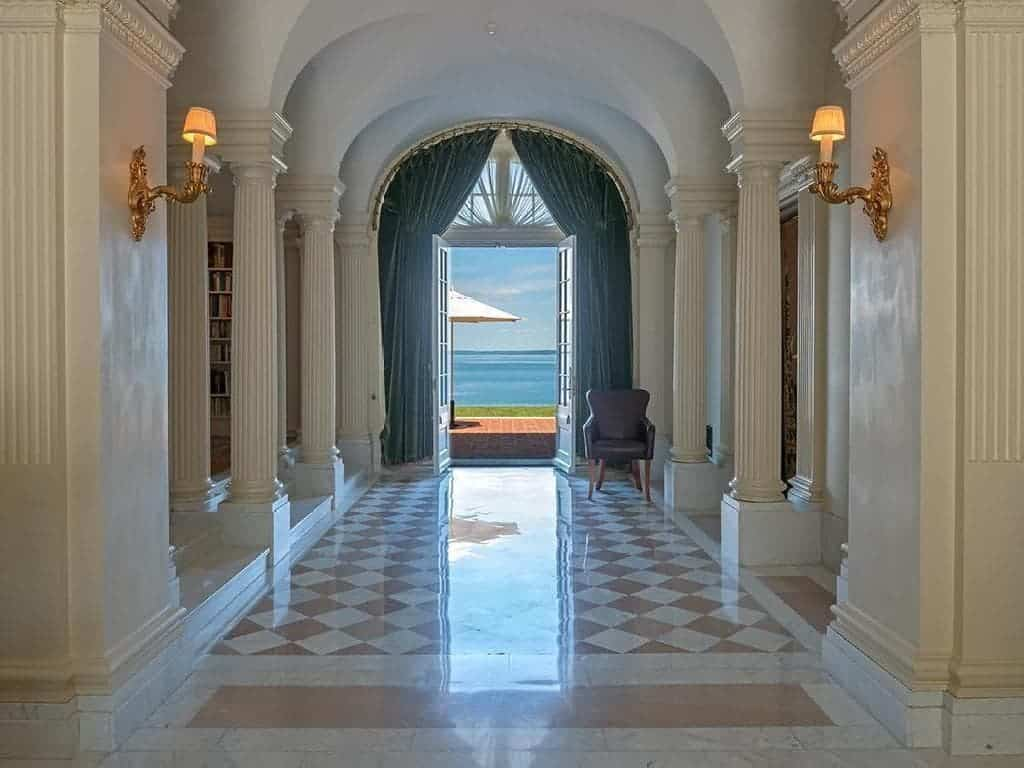 This view of the foyer showcases more of the pillars lining the sides to support the arched entryways and groin-arched ceiling. The hallway also goes further to a back exit. Images courtesy of Toptenrealestatedeals.com.
