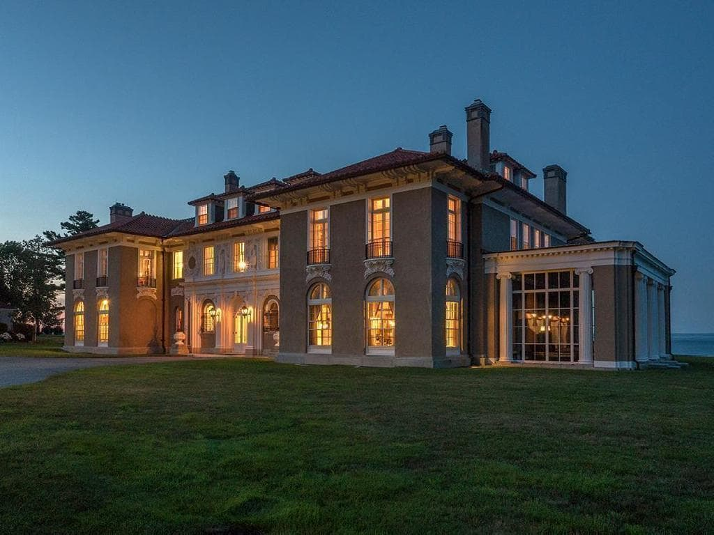 This night time view of the house shows that it glows warmly with the yellow lights coming from the interiors. You can also see here the towering chimneys above and the lush green lawn before the mansion. Images courtesy of Toptenrealestatedeals.com.