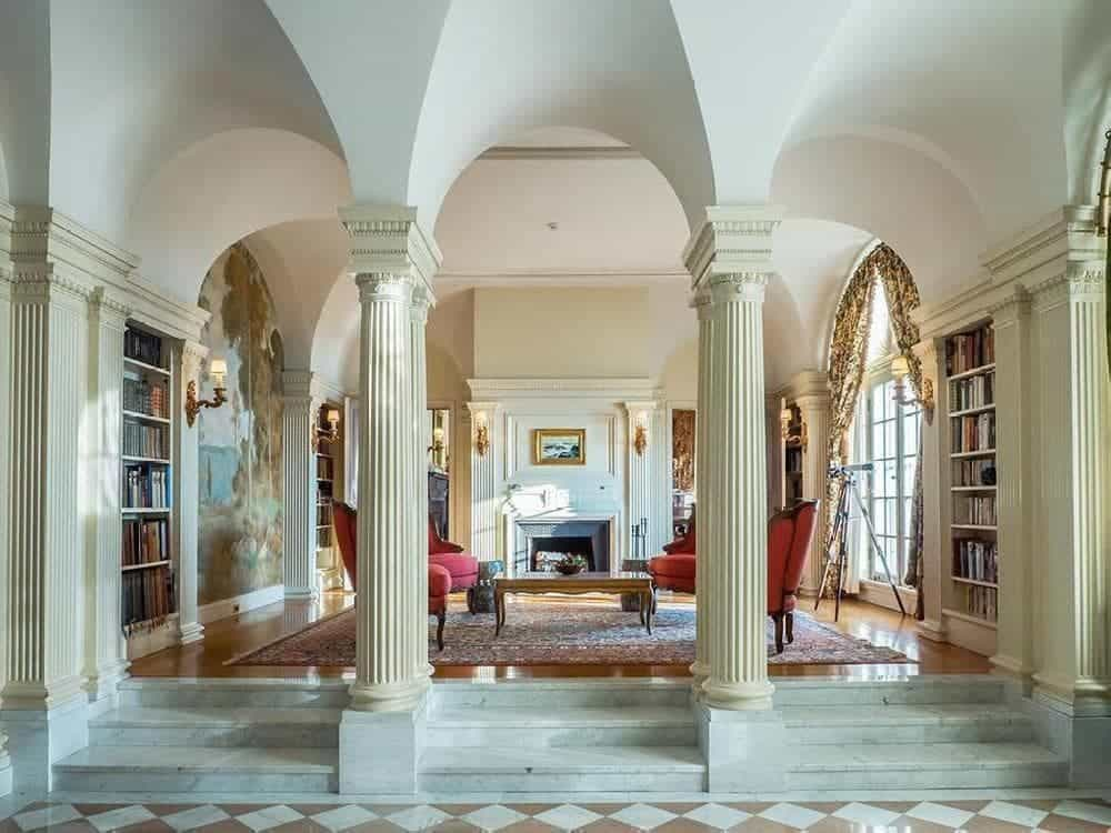 From the foyer, is this living room that has gorgeous built-in bookshelves and a large arched wall adorned with a colorful and elegant painted mural. Images courtesy of Toptenrealestatedeals.com.