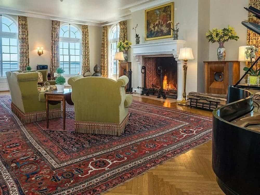 This living room has a warm and homey feel to its large fireplace with white mantle topped by a colorful painting. Across from this is a couple of cushioned arm chairs that stand out on the large colorful patterned area rug over the hardwood flooring. Images courtesy of Toptenrealestatedeals.com.
