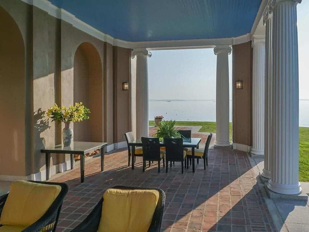 The easr-side porch of the house has a large covered area with terracotta flooring that complements the outdoor dining area on the far end that has a dark tone. These are are all augmented by tall white columns and a tall ceiling with a sky blue hue. Images courtesy of Toptenrealestatedeals.com.