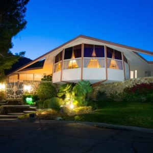 This is the front view of the lovely futuristic mid-century modern house with a unique design beautifully foregrounded with lush landscaping that is complemented by the warm lights of both interior and exterior. Images courtesy of Toptenrealestatedeals.com.