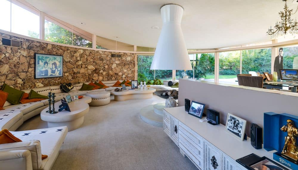 This is the large circular great room that starts from the foyer, to the living room and to the glass walls that lead to the pool side area. here you can see the living room with built-in cushioned seats curving around the large circular modern fireplace in the middle. Images courtesy of Toptenrealestatedeals.com.
