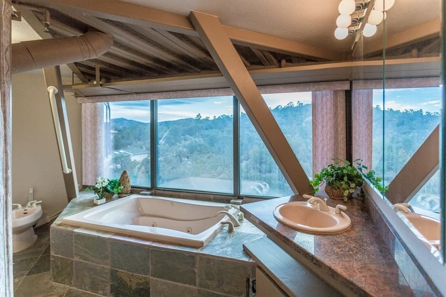This bathroom has a floating vanity with a marble countertop that houses the small sink. Next to it is the small square bathtub that is inlaid with tiles next to the large glass wall for a gorgeous mountaintop view. Images courtesy of Toptenrealestatedeals.com.