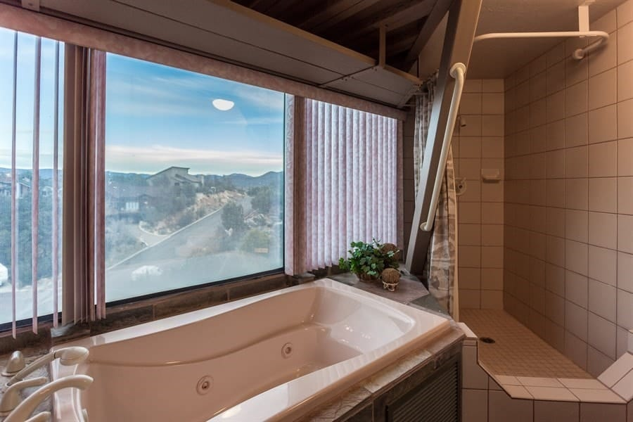 This other bathroom has a large porcelain bathtub next to the glass wall on one side and the walk-in shower area on the far corner with tiled walls. Images courtesy of Toptenrealestatedeals.com.